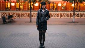 portrait de Temps-faute de femme asiatique sérieuse dans des vêtements élégants se tenant dans la rue le soir et regardant banque de vidéos