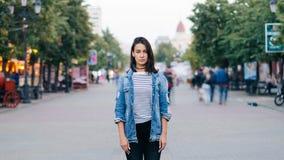 portrait de Temps-faute de l'étudiante fatiguée seul se tenant au centre de la ville et regardant l'appareil-photo avec le sérieu banque de vidéos