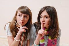 Portrait de tenir des doigts sur des lèvres dans de belles amies du silence 2 ayant l'amusement regardant ensemble l'appareil-pho Image stock