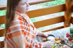 Portrait de thé potable de belle fille blonde dans le jardin d'automne enveloppez-vous dans une couverture, en gros plan photos stock