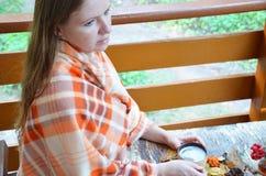 Portrait de thé potable de belle fille blonde dans le jardin d'automne enveloppez-vous dans une couverture, en gros plan images libres de droits