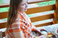 Portrait de thé potable de belle fille blonde dans le jardin d'automne enveloppez-vous dans une couverture, en gros plan image libre de droits