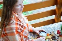 Portrait de thé potable de belle fille blonde dans le jardin d'automne enveloppez-vous dans une couverture, en gros plan images stock