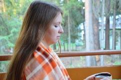 Portrait de thé potable de belle fille blonde dans le jardin d'automne enveloppez-vous dans une couverture, en gros plan image stock