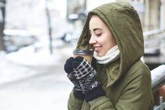 Portrait de thé potable de jeune femme dehors à la rue d'hiver Images stock