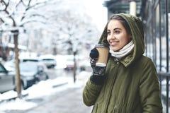 Portrait de thé potable de jeune femme dehors à la rue d'hiver Image libre de droits