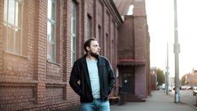Portrait de tir moyen d'homme européen barbu Le mâle dans la veste en cuir regarde à gauche, hésitation, nerveuse Mur de briques  clips vidéos