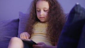 Portrait de tir de nuit d'un enfant mignon caucasien, petite fin de bébé du visage d'un enfant regardant une tablette avec a banque de vidéos