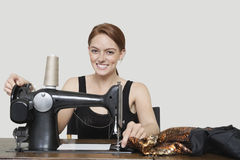 Portrait de tissu piquant de jeune tailleur féminin sur la machine à coudre au-dessus du fond coloré Photos stock