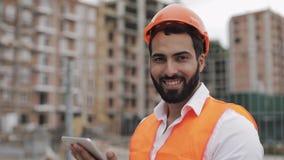 Portrait de travailleur de la construction sur le chantier avec le comprimé regardant la caméra Fin vers le haut Professions, con banque de vidéos