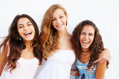 Portrait de trois adolescentes se penchant contre le mur Image stock