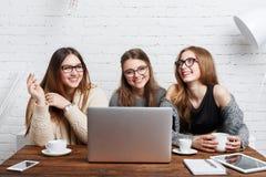 Portrait de trois amies riantes avec l'ordinateur portable Photo stock