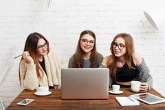 Portrait de trois amies riantes avec l'ordinateur portable Image stock