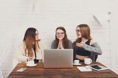 Portrait de trois amies riantes avec l'ordinateur portable Image libre de droits
