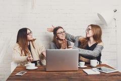 Portrait de trois amies riantes avec l'ordinateur portable Photo libre de droits