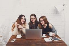 Portrait de trois amies riantes avec l'ordinateur portable Images stock