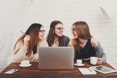Portrait de trois amies riantes avec l'ordinateur portable Photographie stock