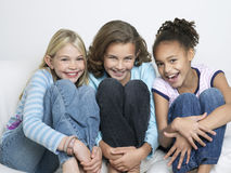 Portrait de trois amis étreignant des genoux Images stock