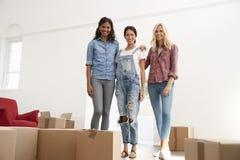 Portrait de trois amis féminins entrant dans la nouvelle maison ensemble Photo stock