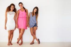 Portrait de trois amis féminins se penchant contre le mur Image libre de droits