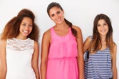 Portrait de trois amis féminins se penchant contre le mur Photographie stock libre de droits
