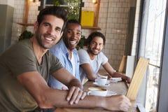 Portrait de trois amis masculins se réunissant dans le café Images stock
