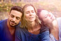 Portrait de trois amis s'asseyant dehors au soleil Photos libres de droits