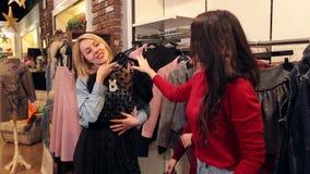 Portrait de trois belles jeunes femmes faisant des emplettes dans un magasin de vêtements banque de vidéos