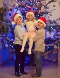 Portrait de trois enfants heureux ayant l'amusement au réveillon de Noël Photo libre de droits