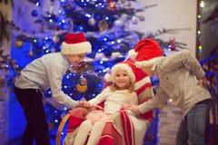 Portrait de trois enfants heureux ayant l'amusement au réveillon de Noël Photos libres de droits