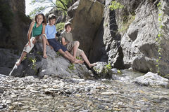 Portrait de trois enfants s'asseyant sur la roche Photographie stock libre de droits