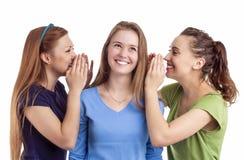 Portrait de trois femelles caucasiennes heureuses partageant des secrets et le RU Photo libre de droits
