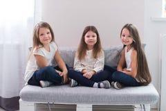 Portrait de trois filles heureuses s'asseyant sur le sofa et le concept d'amitié Photos libres de droits