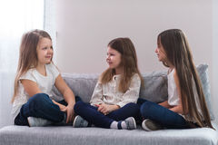 Portrait de trois filles heureuses s'asseyant sur le sofa et le concept d'amitié Images stock