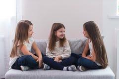 Portrait de trois filles heureuses s'asseyant sur le sofa et le concept d'amitié Image libre de droits