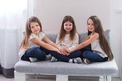 Portrait de trois filles heureuses s'asseyant sur le sofa et le concept d'amitié Photographie stock