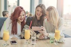 Portrait de trois jeunes belles femmes à l'aide du téléphone portable à la Co Images stock