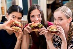 Portrait de trois jeunes femmes mangeant des hamburgers Photo stock