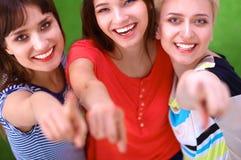 Portrait de trois jeunes femmes, se tenant ensemble et vous dirigeant Image stock