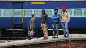 Portrait de trois jeunes hommes à la station de train, avec des personnes passant par elles clips vidéos