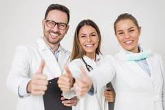Portrait de trois médecins heureux qui se tiennent souriants et montrent le pouce Image stock