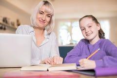 Portrait de tuteur à la maison féminin Helping Young Girl avec des études photo stock