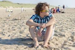 Portrait de type adolescent se reposant sur le sable Photographie stock