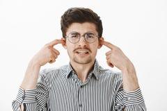 Portrait de type ordinaire de pleurnicherie de renversement dans les verres ronds et la chemise rayée, couvrant des oreilles d'in Image libre de droits