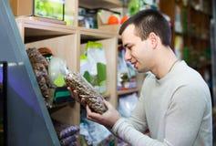 Portrait de type sélectionnant la nourriture de vétérinaire dans le petshop Images stock