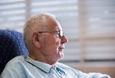 Portrait de vieil homme dans des pyjamas sur le sofa Images libres de droits