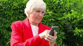 Portrait de vieille dame, téléphone d'utilisation de grand-mère dehors au jour du soleil contact moderne de doigt de mamie l'?cra clips vidéos