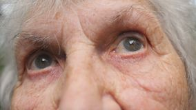 Portrait de vieille grand-mère recherchant Fermez-vous vers le haut des yeux d'une femme agée avec des rides autour de elles banque de vidéos