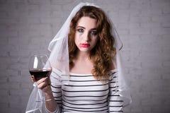 Portrait de vin pleurant et potable triste de jeune mariée Photos stock