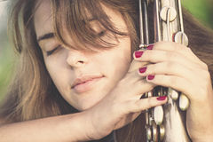 Portrait de vintage de jeune femme avec l'instrument de musique de vent dans la main sur la pelouse Image libre de droits